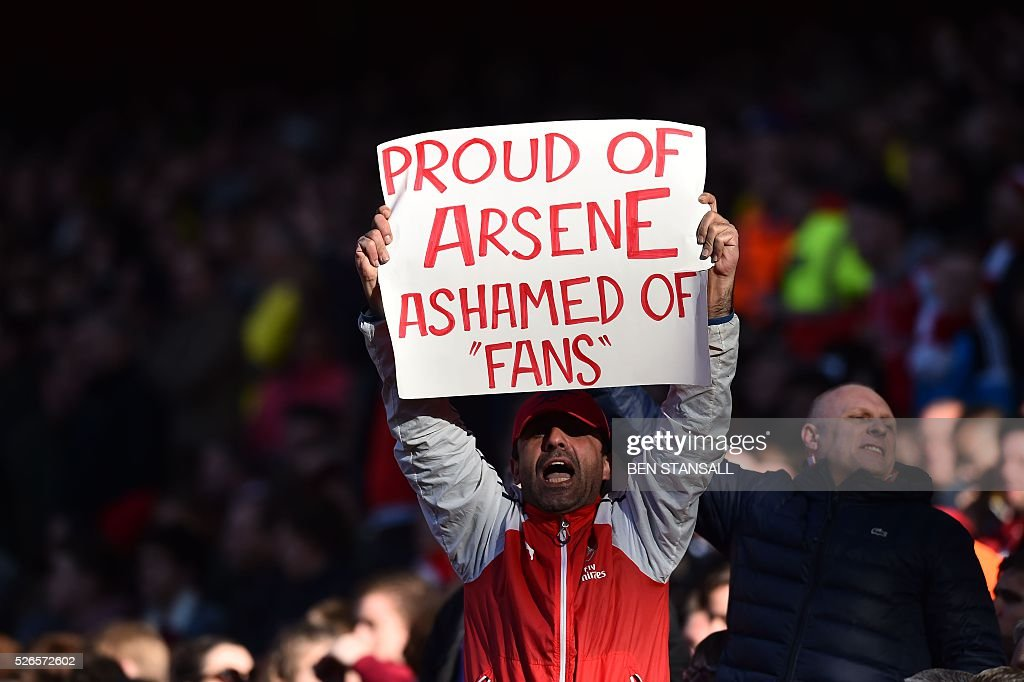 An Arsenal fan holds up a sign that reads 'Proud of Arsene, ashamed of fans', in a show of support for Arsenal's French manager Arsene Wenger, and a counter demonstration against those fans calling for change at the football club, during the English Premier League football match between Arsenal and Norwich at the Emirates Stadium in London on April 30, 2016. / AFP / BEN STANSALL / RESTRICTED TO EDITORIAL USE. No use with unauthorized audio, video, data, fixture lists, club/league logos or 'live' services. Online in-match use limited to 75 images, no video emulation. No use in betting, games or single club/league/player publications. /