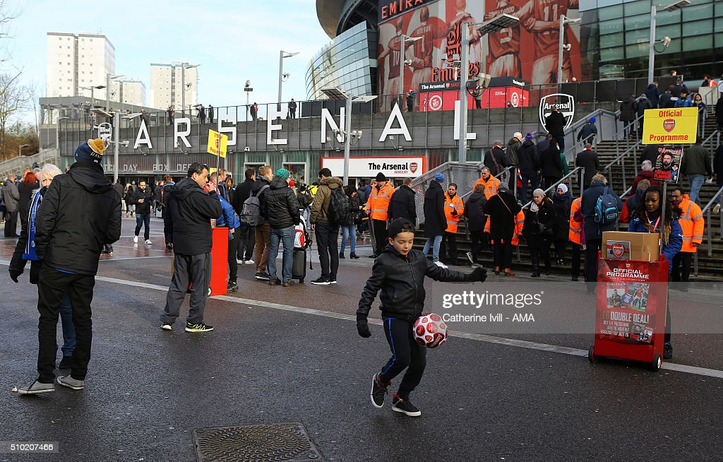 An Arsenal fan plays football outside the stadium before the Barclays Premier League match between Arsenal and Leicester City at the Emirates Stadium on February 14, 2016 in London, England.