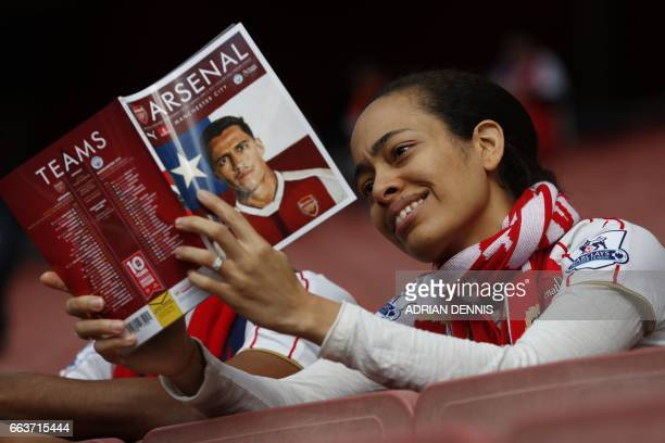 An Arsenal fan reads the match programme waiting for kick off of the English Premier League football match between Arsenal and Manchester City at the...