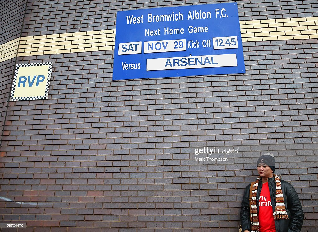 An Arsenal fan stands outside the ground prior to the Barclays Premier League match between West Bromwich Albion and Arsenal at The Hawthorns on...