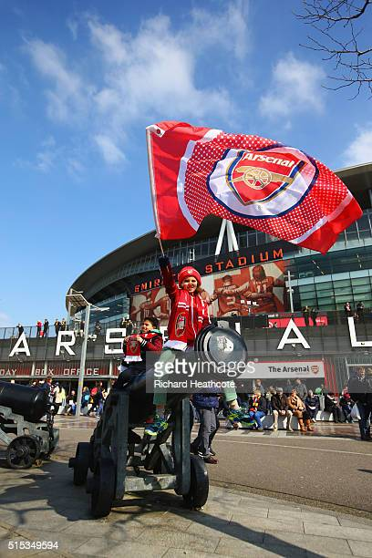 An Arsenal fan waves a flag outside the stadium prior to the Emirates FA Cup sixth round match between Arsenal and Watford at Emirates Stadium on...