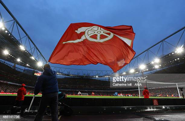 An Arsenal flag is waved before the Barclays Premier League match between Arsenal and Liverpool at the Emirates Stadium on August 24 2015 in London...