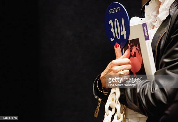 An art buyer holds a catalogue at the Sotheby's auction of important Australian paintings May 7 2007 in Sydney Australia