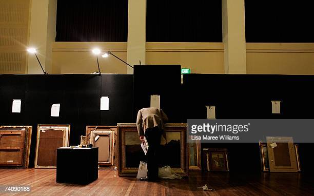 An art buyer inspects works backstage at the Sotheby's auction of important Australian paintings May 7 2007 in Sydney Australia