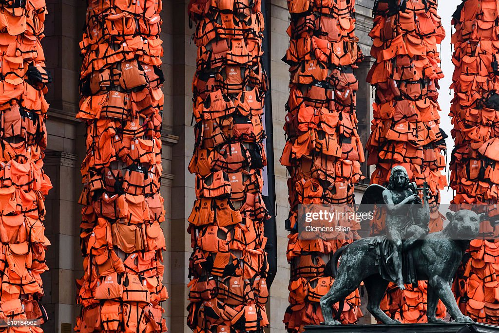 An art installation by Chinese artist Ai Weiwei that consists of life vests worn by refugees bound to the columns of the concert house next to a statue at Gendarmenmarkt on February 14, 2016 in Berlin, Germany. The life vests were among the thousands discarded by migrants and refugees after they crossed the sea from Turkey to Greece. Ai Weiwei lives in Berlin and is currently involved in several projects relating to refugees. Up to 80,000 refugees currently live in Berlin and the city is preparing for the likely arrival of 30,000 more in 2016.