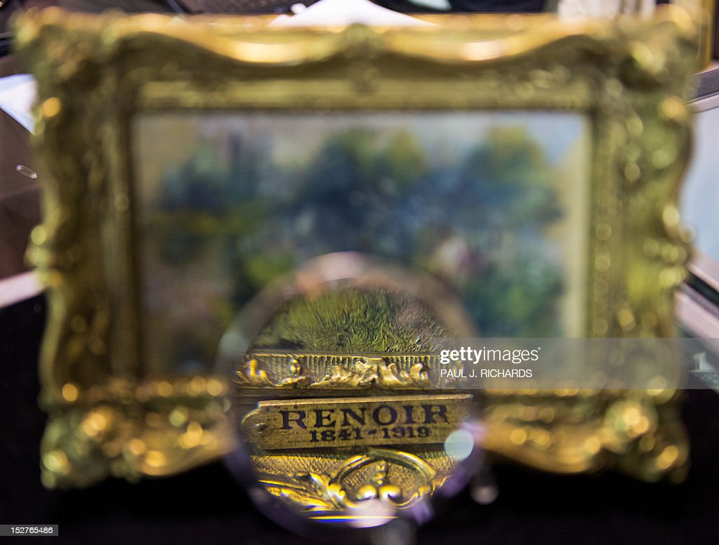 An art shopper looks closely at a 5.5 inch by 6.6 inch (14 centimeter by 23 centimeter) painting by French Impressionist master Pierre-Auguste Renoir September 25, 2012 in Alexandria, Virginia. The painting was recently discovered for just a few dollars at a Virgina flea market sale. The canvas which shows a scene along the Seine River titled 'Paysage Bords de Seine' is scheduled to be auctioned September 29, 2012 at the Potomack Company, in Alexandria, Virginia, selling for an expected 75,000 to 100,000 USD. It was for sale in a box with a plastic cow and a Paul Bunyan doll for 50.00 USD and still carries a label from the Berheim-Jeune arthouse in Paris, a famous purveyor of works by Renoir. AFP PHOTO/Paul J. Richards