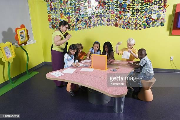 An art teacher observing her students drawing in art class