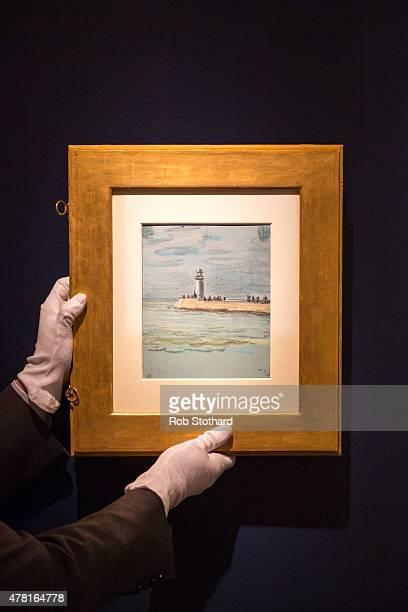 An art technician holds 'La Jetee' a verso piece on Claude Monet's 1968 piece 'Etude de ceil' at the Richard Green stand at Masterpiece Fair on June...