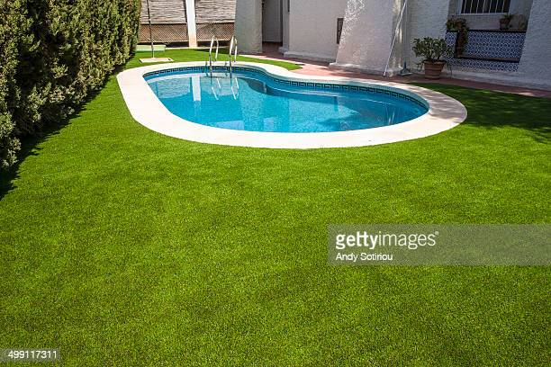 An artificial lawn around a swimming pool