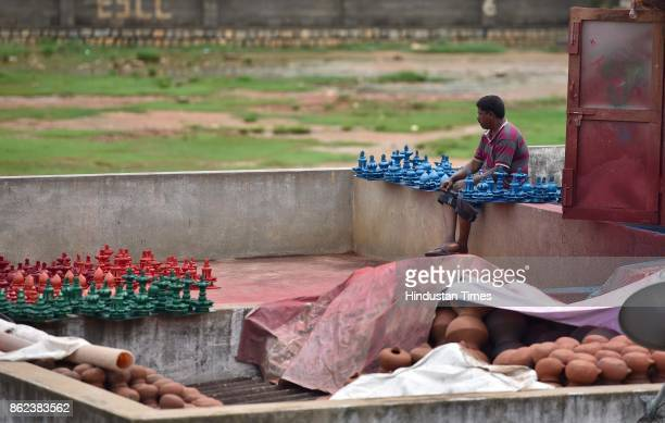 An artisan drying earthen lamps at Pottery Town on October 12 2017 in Bengaluru India Pottery Town is a patch of clay amid the City of Garden It's...