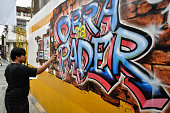 An artist apply finishing touches in his mural painting during the Obra sa Pader Mural Painting Competition in Makati City on Sunday The mural...