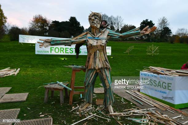 An artist builds a figure out of wooden pieces at the Rheinaue park during the COP23 United Nations Climate Change Conference in Bonn Germany / AFP...