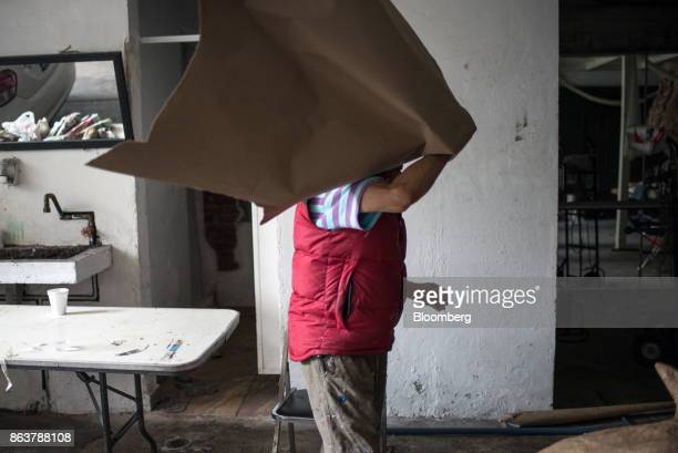 An artist carries paper to create a giant alebrije Mexican folk art sculpture at a studio in Mexico City Mexico on Monday Oct 16 2017 The first...