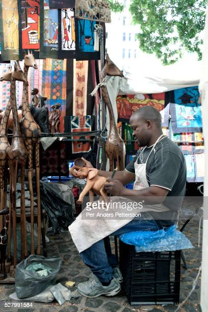 An artist carves a wooden elephant at Greenmarket Square market on March 21 2012 in Cape Town South Africa