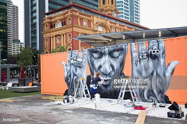 An artist creats a mural on a boxcar.