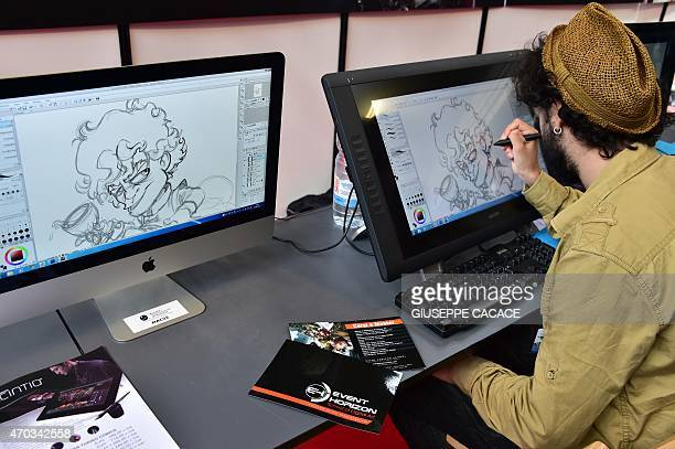An artist draws a cartoon on a screen during the 'Torino Comics' book fair at Lingotto Fair on April 19 2015 in Turin AFP PHOTO / GIUSEPPE CACACE