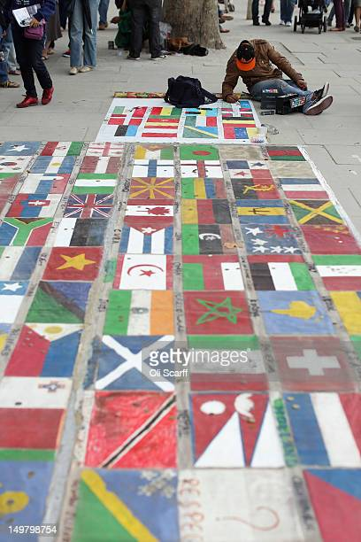 An artist draws flags of the world on which people are encouraged to lay money on the South Bank on August 4 2012 in London England