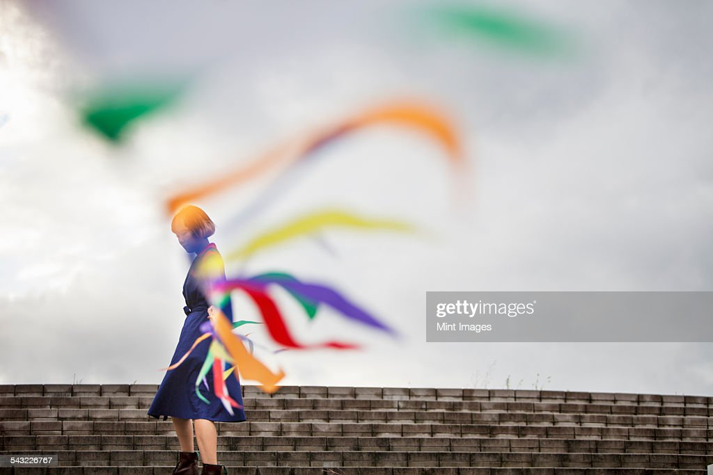 An artist during a performance moving a line of flags or streamers. : Stock-Foto