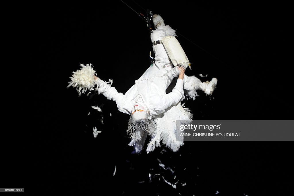 An artist from the Studio de Cirque company performs in the sky during 'Place des Anges' at the Cours d'Estienne d'Orves in Marseille on January 12, 2013, one of the events marking the launching of festivities for the Marseille-Provence 2013 European Capital of Culture. The event marks the start of a year of cultural renaissance in France's second-largest metropolitan area. AFP PHOTO / ANNE-CHRISTINE POUJOULAT