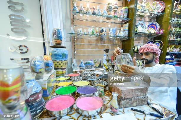 An artist hand painting and decorating a glass inside a shop with souvenirs inside a Dubai mall in Dubai downtown On Monday 6 February in Dubai UAE