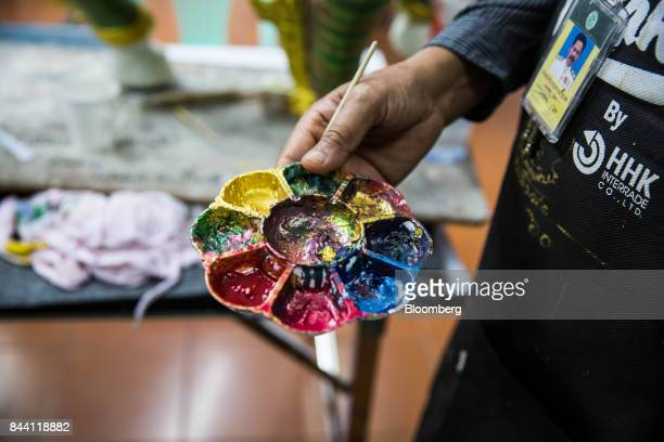 An artist holds his palette of paint while working on a decorative item for the cremation ceremony of King Bhumibol Adulyadej in a studio at the Fine...