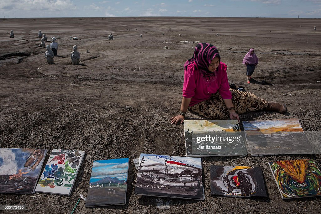 An artist, Novi, holds her painting at mudflow during the tenth anniversary of the mudflow eruption on May 29, 2016 in Sidoarjo, East Java, Indonesia. Residents of villages which were damaged by the Sidoarjo mudflow have finally received compensation from the Indonesian oil and gas company, PT Lapindo Brantas, after almost ten years. The mudflow eruption is suspected to have been triggered by the drilling activities of the oil and gas company, though they refute the claims, instead blaming a 6.3 magnitude earthquake which struck the neighbouring city of Yogyakarta, a city 150 miles west of a drill site in Sidoarjo, two days before the mudflow eruption on May 27th, 2006. According to reports, twenty lives were lost and nearly 40,000 people displaced, with damages topping USD 2.7 billion. Ten years on since the eruption the mud geysers still continue to spurt mud out on a daily basis and high levels of heavy metals have been detected in nearby rivers.