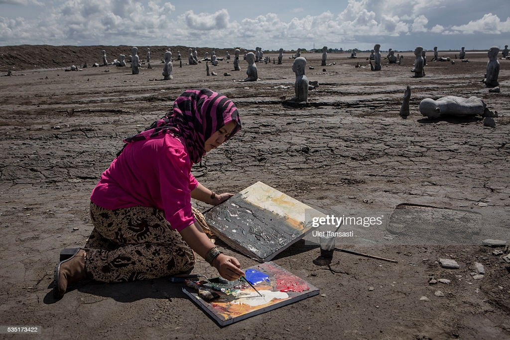 An artist, Novi, paints at mudflow during the tenth anniversary of the mudflow eruption on May 29, 2016 in Sidoarjo, East Java, Indonesia. Residents of villages which were damaged by the Sidoarjo mudflow have finally received compensation from the Indonesian oil and gas company, PT Lapindo Brantas, after almost ten years. The mudflow eruption is suspected to have been triggered by the drilling activities of the oil and gas company, though they refute the claims, instead blaming a 6.3 magnitude earthquake which struck the neighbouring city of Yogyakarta, a city 150 miles west of a drill site in Sidoarjo, two days before the mudflow eruption on May 27th, 2006. According to reports, twenty lives were lost and nearly 40,000 people displaced, with damages topping USD 2.7 billion. Ten years on since the eruption the mud geysers still continue to spurt mud out on a daily basis and high levels of heavy metals have been detected in nearby rivers.