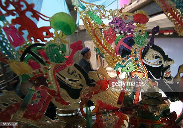 An artist of a folk art troupe is seen through leather puppets as he plays an accompaniment with traditional music instrument during a Chinese Shadow...