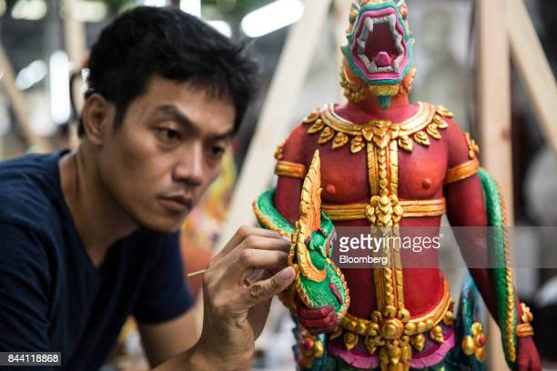 An artist paints a decorative item for the cremation ceremony of King Bhumibol Adulyadej in a studio at the Fine Arts Department in Bangkok Thailand...