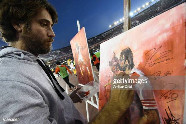 An artist paints a portrait of Fernando Cavenaghi during Fernando Cavenaghi's farewell match at Monumental Stadium on July 01 2017 in Buenos Aires...