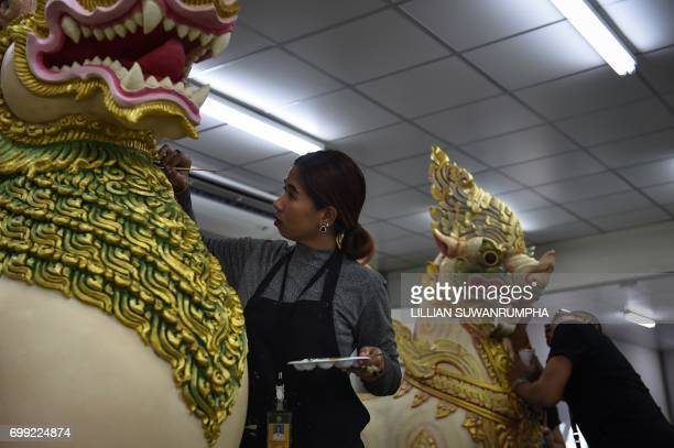An artist paints a statue of a Rajasi or mythical lion in a warehouse next to the funeral pyre and surrounding pavilions for the late Thai King...