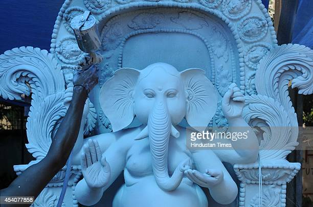 An artist paints a statue of Lord Ganesha at a workshop ahead of Ganesha Chathurthi festival on August 24 2014 in Noida India The district...