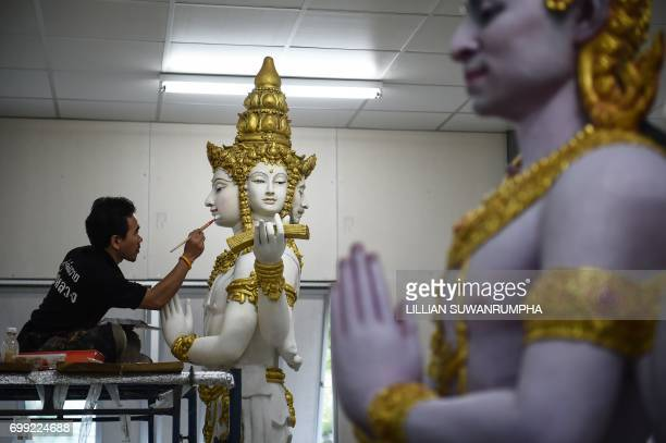 An artist paints a statue of the fourheaded god Brahma in a warehouse next to the funeral pyre and surrounding pavilions for the late Thai King...