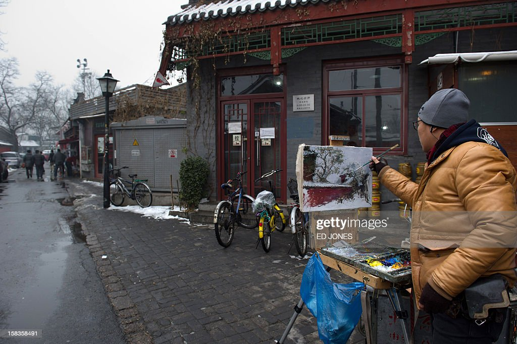 An artist paints an image of a 'hutong' area near the 13th century historic Drum and Bell Tower in Beijing on December 14, 2012. China's capital is to destroy swathes of ancient courtyard homes around a 13th-century landmark in what is being called an effort to preserve Beijing's historical legacy, residents said. Large numbers of hutong homes, some of them dating back to the Qing dynasty, will be demolished around the Drum and Bell Tower -- a tourist hotspot in Beijing's historic centre -- to make way for a large plaza, they said. AFP PHOTO / Ed Jones
