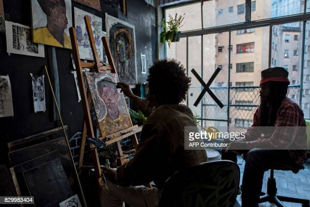 An artist paints in his atelier at the 'Ocupa Ouvidor 63' building in Sao Paulo Brazil on June 28 2017 A group of about one hundred artists of...