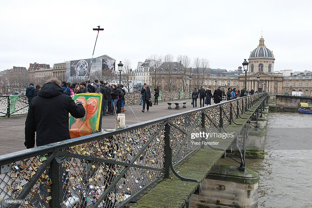 An artist paints on the Pont des Arts on January 4, 2013 in Paris, France. The nine-arch metallic footbridge completed in 1804 is one of the most romantic places of the capital where people visit it to attach love padlocks illustrated with their initials or messages of love, before throwing the key into the River Seine. The bridge is also a meeting place for artists who find inspiration from the surrounding views of the city.