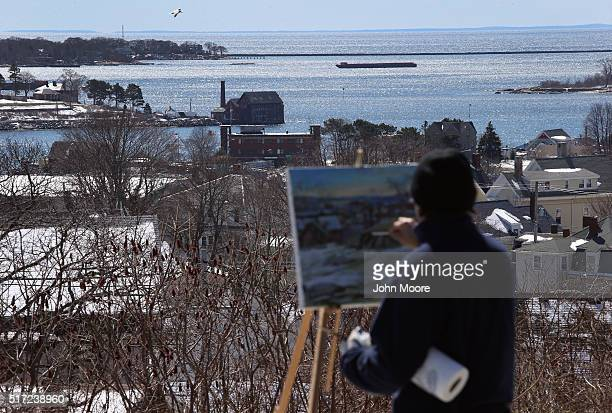 An artist paints the Gloucester Harbor on March 22 2016 in Gloucester MA Gloucester and communities across New England are struggling with an...
