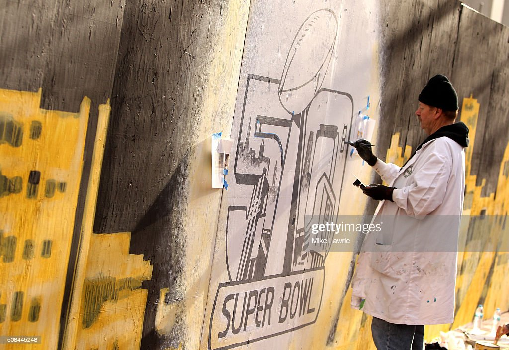 An artist paints the Super Bowl 50 logo along Market Street prior to Super Bowl 50 on February 4, 2016 in San Francisco, United States.