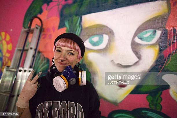 An artist poses for a photograph as more than 100 graffiti artists attempt a Guinness world record to create the largest spray paint mural by...