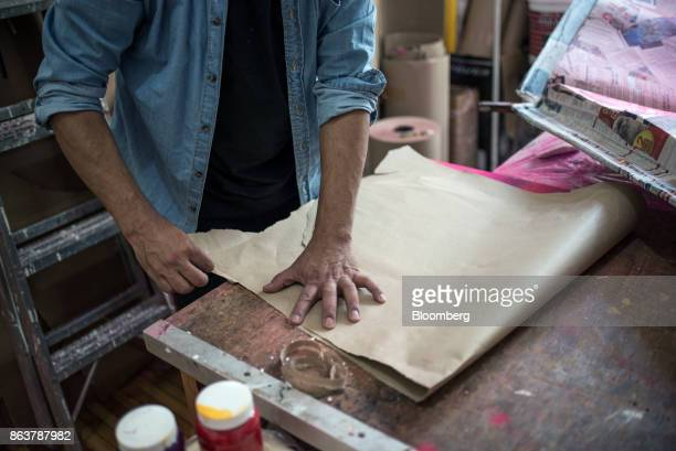 An artist prepares a piece of paper to create a giant alebrije Mexican folk art sculpture at the Mauricio Mercado y Compaia collective studio in...