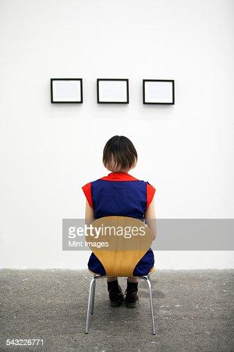 An artist sitting on a chair, looking at an artwork.
