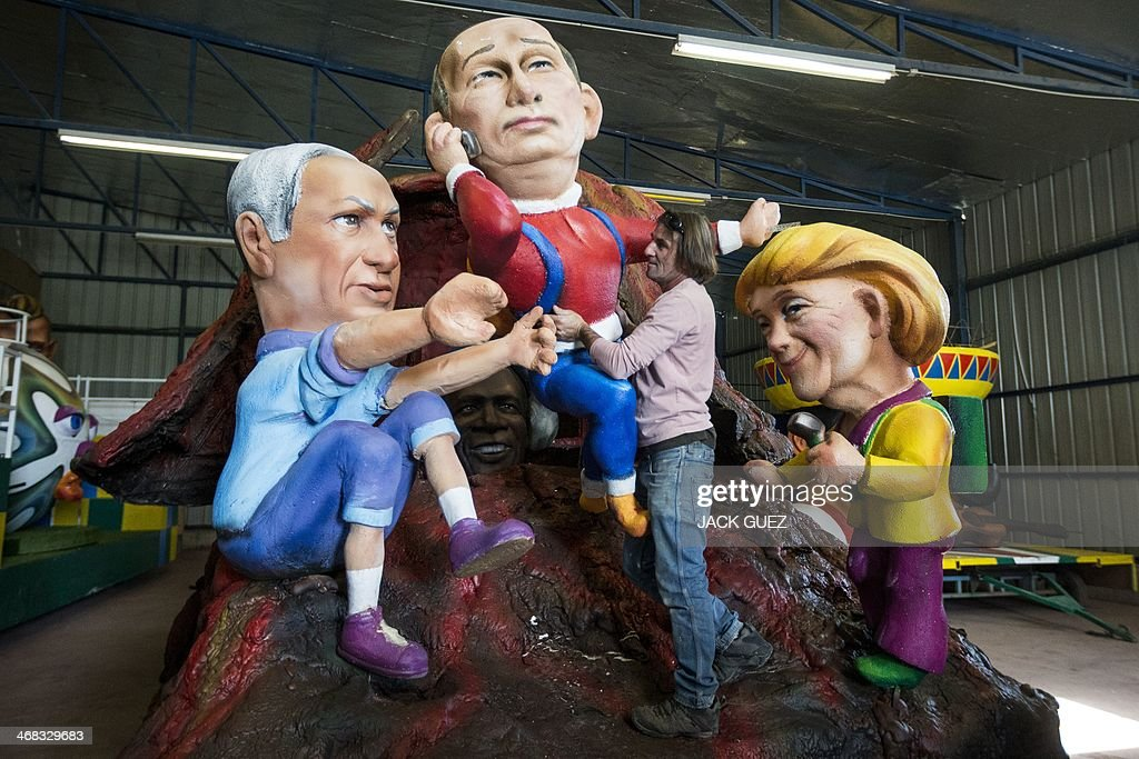 An artist stands amid effigies of Israeli Prime Minister Benjamin Netanyahu(L), Russian President Vladimir Putin (C) and German Chancellor Angela Merkel (R), during preparations for the Jewish festivities of Purim, on February 10, 2014 in the Israeli central town of Jaljulia. The carnival-like Purim holiday starts on March 16, with parades and costume parties to commemorate the deliverance of the Jewish people from a plot to exterminate them in the ancient Persian Empire 2,500 years ago, as described in the Book of Esther.