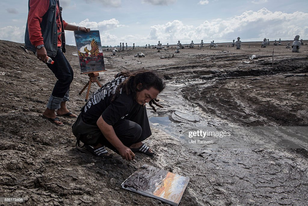 An artist using mud to paints as they take action paint together at mudflow during the tenth anniversary of the mudflow eruption on May 29, 2016 in Sidoarjo, East Java, Indonesia. Residents of villages which were damaged by the Sidoarjo mudflow have finally received compensation from the Indonesian oil and gas company, PT Lapindo Brantas, after almost ten years. The mudflow eruption is suspected to have been triggered by the drilling activities of the oil and gas company, though they refute the claims, instead blaming a 6.3 magnitude earthquake which struck the neighbouring city of Yogyakarta, a city 150 miles west of a drill site in Sidoarjo, two days before the mudflow eruption on May 27th, 2006. According to reports, twenty lives were lost and nearly 40,000 people displaced, with damages topping USD 2.7 billion. Ten years on since the eruption the mud geysers still continue to spurt mud out on a daily basis and high levels of heavy metals have been detected in nearby rivers.