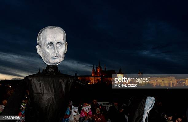 An artist wearing a mask with the face of Russian President Vladimir Putin walks across the Charles Bridge during the carnival commemorating the 26th...