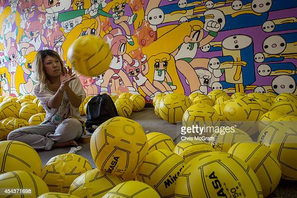 An artist works to blow up 300 volleyballs as part of her art piece in an office building on August 30 2014 in Tokyo Japan The art project 'BCTION'...