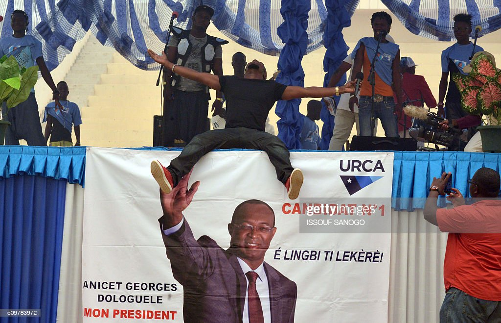 An artiste performs next to Central African Republic second round presidential candidate Anicet Georges Dologuele banner during a presidential campaign at the Bangui stadium on February 12, 2016, ahead of the Febuary 14 presidential and legislatives elections. / AFP / ISSOUF SANOGO
