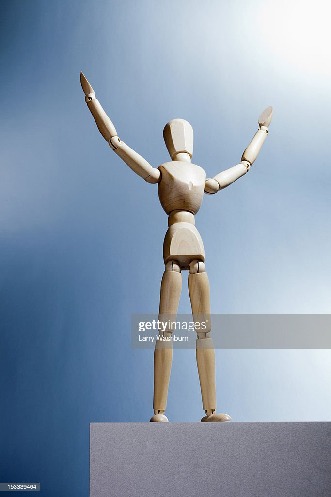 An artist's figure standing atop a box with arms raised and head tilted up