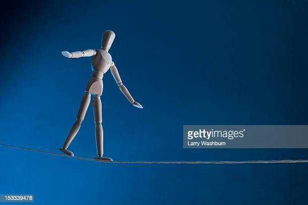 An artist's figure walking a tightrope