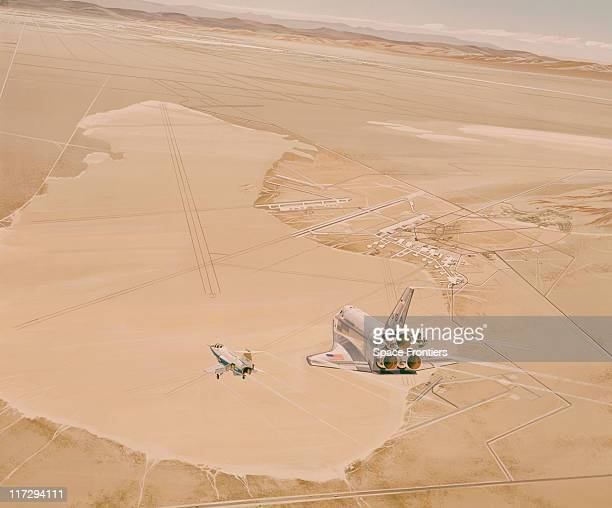 An artist's impression of the prototype Space Shuttle Enterprise accompanied by a chase plane as it comes in to land at Edwards Air Force Base...