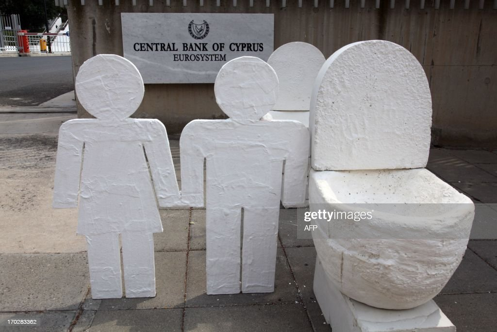 An artwork of plaster toilets by Cypriot artist Andreas Efstathiou is displayed outside the Cyprus Central Bank in Nicosia on June 10, 2013 in an unusual protest to signal the island's bailout economy is going down the pan. Efstathiou called it a 'symbolic protest' to highlight the pain Cypriots have suffered since Cyprus secured 10 billion euros ($13 billion) in European Union rescue aid in return for an unprecedented bail-in from bank depositors.